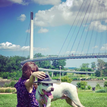 woman and dog in park by pedestrian bridge